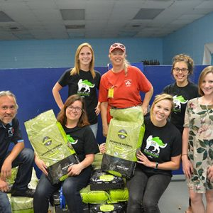 Staff members at Austin Human Society smiling and holding bags of pet food