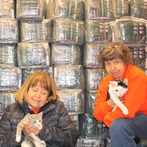 two women holding two cats in front of World's Best Cat Litter