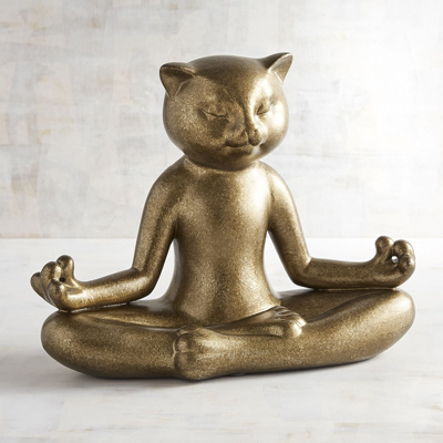 gold statue of cat in yoga pose