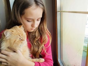 Young girl snuggling cat.